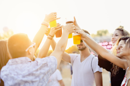 Six people cheering their drinks at an out door event.