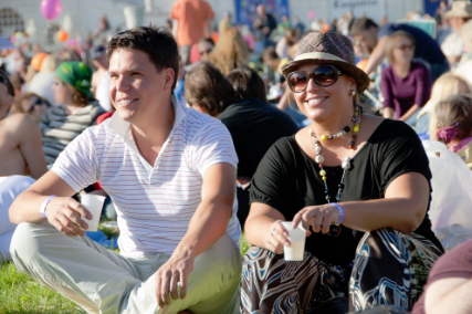 This is a picture of two people sitting down chilling at an out door festival.